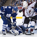 Toronto Maple Leafs goalie James Reimer looks to cover the puck as Colorado Avalanche center Daniel Briere (48) and Maple Leafs' Stuart Percy (50) reach for the puck during the first period of an NHL hockey game Tuesday, Oct. 14, 2014, in Toronto The Asso