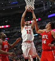 CHICAGO, IL - FEBRUARY 11: Joakim Noah #13 of the Chicago Bulls grabs one of 16 rebounds between Paul Millsap #4 and Gustavo Ayon #14 of the Atlanta Hawks at the United Center on February 11, 2014 in Chicago, Illinois. The Bulls defeated the Hawks 100-85. (Photo by Jonathan Daniel/Getty Images)