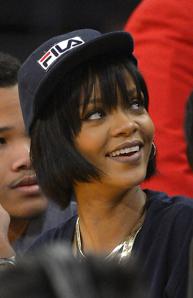 Singer Rihanna, watches the Los Angeles Lakers play the Portland Trail Blazers in an NBA basketball game, Sunday, Dec. 1, 2013, in Los Angeles