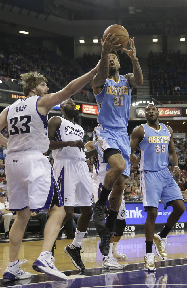 Denver Nuggets Wilson Chandler, center, drives to the basket against Sacramento Kings' Aaron Gray, left, and Quincy Acy, second from left, as Nuggets forward Kenneth Faried, right, looks on during the first quarter of an NBA basketball game in Sacramento, Calif., Sunday, Jan. 26, 2014