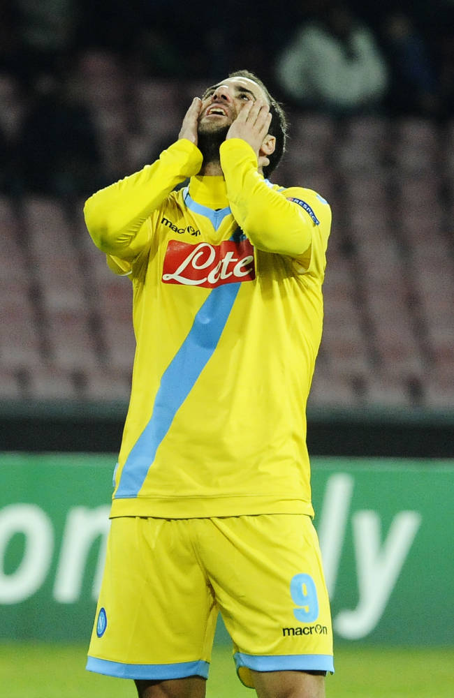 Napoli's Gonazalo Higuain looks up at the end of a Champions League, group F, soccer match between Napoli and Arsenal, at the Naples San Paolo stadium, Italy, Wednesday, Dec. 11, 2013. Ten-man Arsenal advanced to the Champions League knockout phase for the 14th consecutive year despite a 2-0 loss Wednesday at Napoli, which was eliminated. Gonzalo Higuain scored in the 73rd minute but the San Paolo stadium was soon silenced when word arrived that Borussia Dortmund had scored a late goal in a 2-1 win at Marseille to win Group F