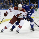 Arizona Coyotes center Martin Hanzal (11), of the Czech Republic, carries the puck past Tampa Bay Lightning defenseman Jason Garrison (5) during the first period of an NHL hockey game Tuesday, Oct. 28, 2014, in Tampa, Fla The Associated Press