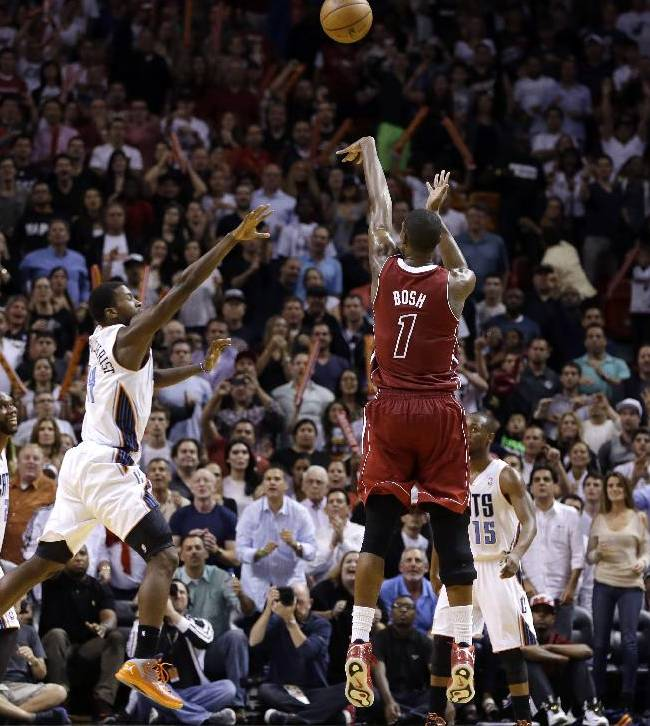 Miami Heat's Chris Bosh (1) shoots a three-point jumper over Charlotte Bobcats' Michael Kidd-Gilchrist to put the Heat ahead in the fourth quarter of an NBA basketball game Sunday, Dec. 1, 2013, in Miami. The Heat won 99-98
