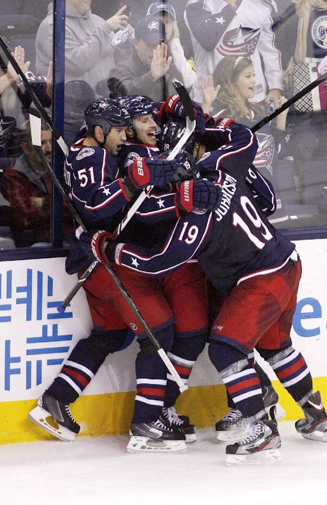Columbus teammates mob R.J. Umberger after he scored the game-winning goal against Vancouver during the third period of an NHL hockey game Sunday, Oct. 20, 2013, in Columbus, Ohio