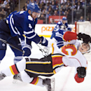 Toronto Maple Leafs defenceman Cody Franson (4) hits Calgary Flames forward Johnny Gaudreau (13) during the third period of an NHL hockey game in Toronto on Tuesday, Dec. 9, 2014 The Associated Press
