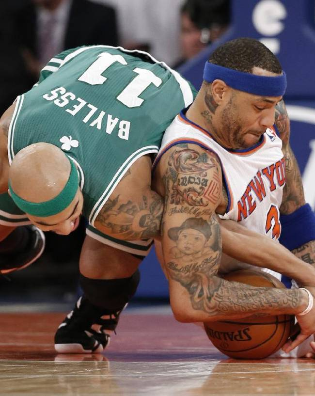 Boston Celtics guard Jerryd Bayless (11) and New York Knicks forward Kenyon Martin (3) battle for a loose ball in the first half of an NBA basketball game at Madison Square Garden in New York, Tuesday, Jan. 28, 2014
