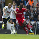 Tottenham Hotspur's Younes Kaboul vies for the ball with Liverpool's Mario Balotelli, during their English Premier League soccer match at White Hart Lane, London, Sunday, Aug. 31, 2014