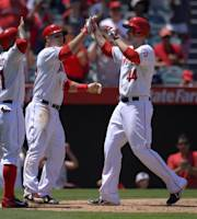Los Angeles Angels' Mark Trumbo, second from right, is congratulated by Howie Kendrick, left, and Mike Trout, second from left, as Toronto Blue Jays catcher J.P. Arencibia looks on after hitting a three-run home run during the fourth inning of their baseball game, Sunday, Aug. 4, 2013, in Anaheim, Calif. (AP Photo/Mark J. Terrill)