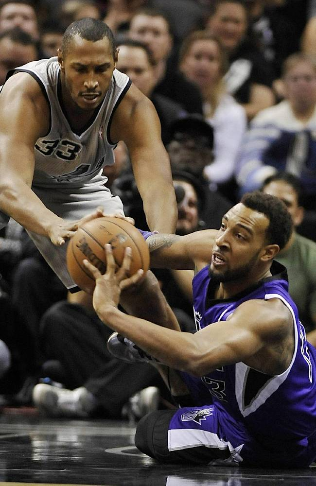 Sacramento Kings forward Derrick Williams, right, fights for the loose ball against San Antonio Spurs forward Boris Diaw, of France, during the first half of an NBA basketball game on Sunday, Dec. 29, 2013, in San Antonio
