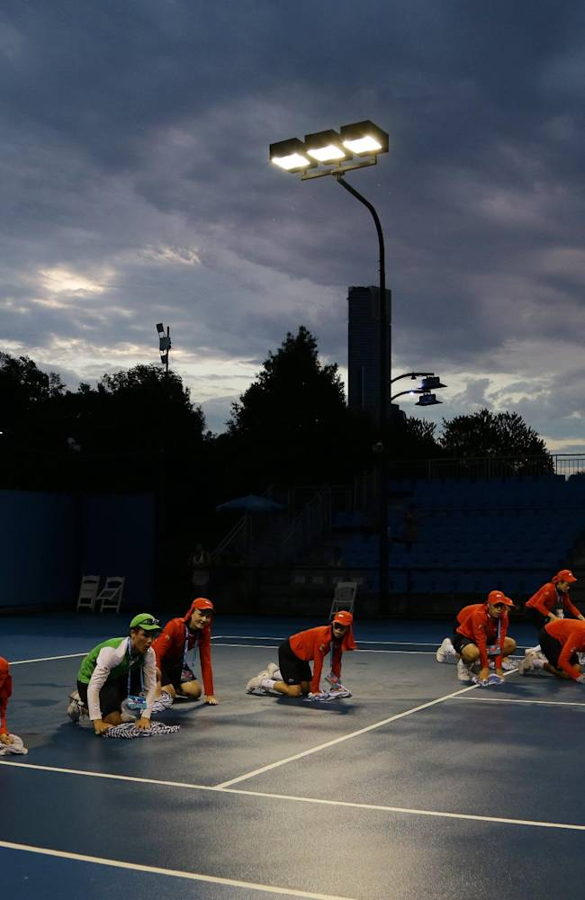 Ball boys dry the surface of an outside court after rain delayed play late in the day at the Australian Open tennis championship in Melbourne, Australia, Thursday, Jan. 16, 2014
