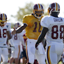 Washington Redskins quarterback Robert Griffin III (10) greets receiver Pierre Garcon after a set of drills during practice at the team's NFL football training facility, Monday, July 28, 2014 in Richmond, Va The Associated Press