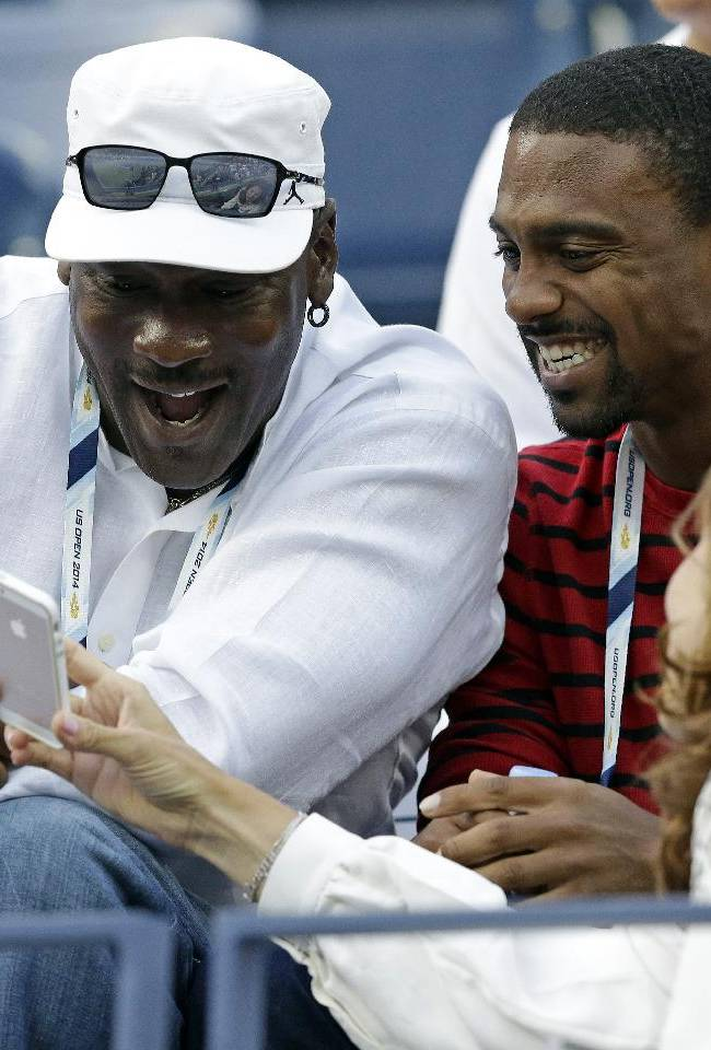 Mirka Federer shows Michael Jordan, left,  photos on her phone before a match between Roger Federer, of Switzerland, and Marinko Matosevic, of Australia, in the first round of the 2014 U.S. Open tennis tournament Tuesday, Aug. 26, 2014, in New York