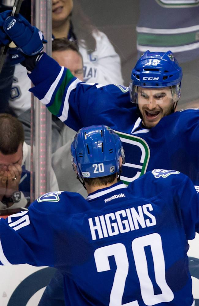 Vancouver Canucks' Brad Richardson, rear, and Chris Higgins celebrate Richardson's goal against the Tampa Bay Lightning as a Lightning fan, left, reacts during the second period of an NHL hockey game against the Vancouver Canucks on Wednesday, Jan. 1, 2014, in Vancouver, British Columbia