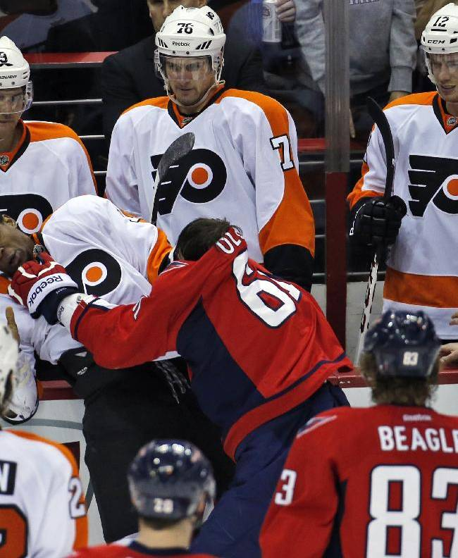 Philadelphia Flyers right wing Wayne Simmonds (17) and Washington Capitals defenseman Steve Oleksy (61) fight in front of the Flyers bench, in the third period of an NHL hockey game, Sunday, Dec. 15, 2013, in Washington. The Capitals won 5-4 in a shootout