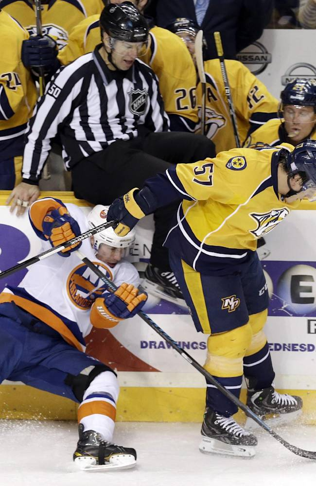 Nashville Predators forward Gabriel Bourque (57) and New York Islanders center Casey Cizikas, left, fight for the puck as linesman 50 Scott Cherrey (50) tries to get out of the way in the first period of an NHL hockey game on Saturday, Oct. 12, 2013, in Nashville, Tenn