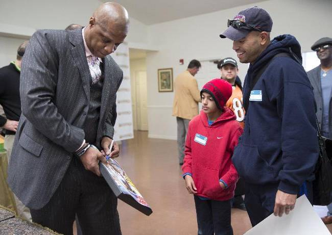 Retired baseball player Darryl Strawberry, left, signs autographs for Angel Alvarez, 10, center and his father Gilbert Alvarez, right, at the grand opening event for the Darryl Strawberry Recovery Center in St. Cloud, Fla., Friday, Jan. 24, 2014. The center features a program aimed at helping athletes address post-playing issues
