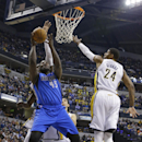 Dallas Mavericks center DeJuan Blair, left, shoots next to Indiana Pacers forward Paul George during the first half of an NBA basketball game in Indianapolis, Wednesday, Feb. 12, 2014 The Associated Press