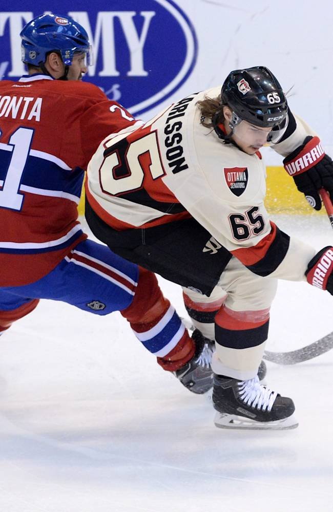 Ottawa Senators defenseman Erik Karlsson, right, dances the puck around Montreal Canadiens' forward Brian Gionta during first period NHL hockey action in Ottawa on Friday, April 3, 2014