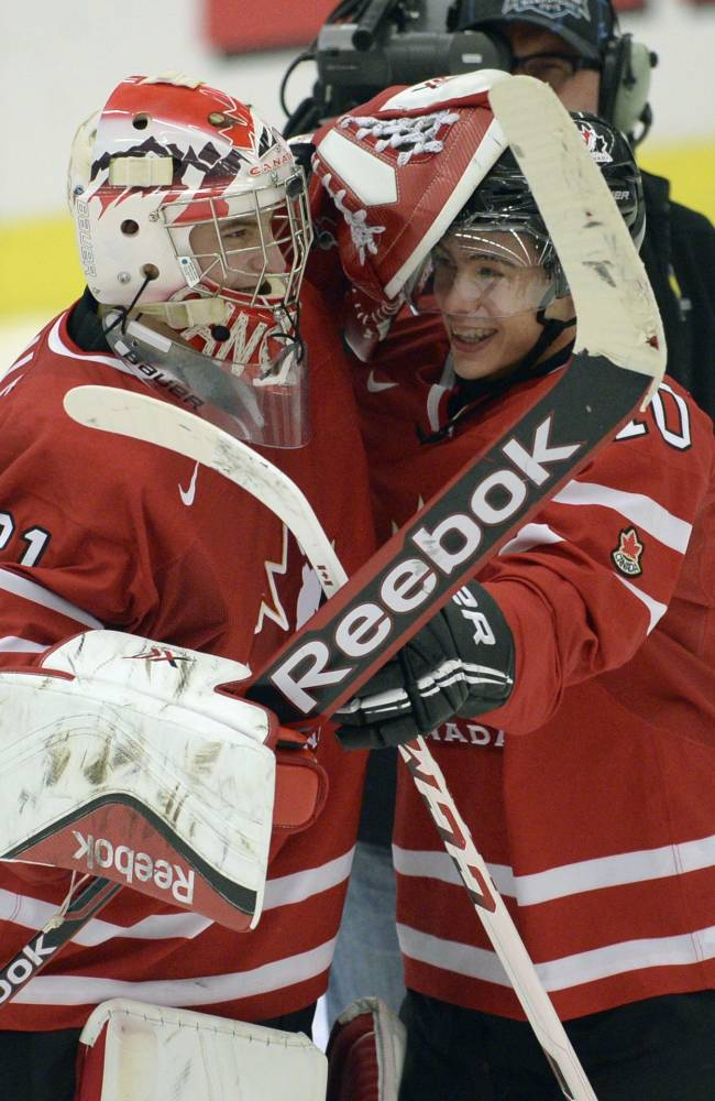 Canada's Zachary Fucale, left, and Charles Hubon celebrate their win over Switzerland in a quarterfinal match at the world junior hockey tournament in Malmo, Sweden, Thursday, Jan 2, 2014. (AP Photo/The Canadian Press, Frank Gunn)