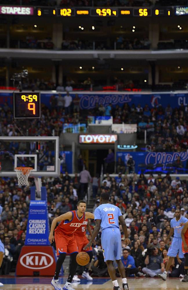 Los Angeles Clippers guard Darren Collison, right, dribbles the ball as they hold a 46-point lead while Philadelphia 76ers guard Michael Carter-Williams defends during the second half of an NBA basketball game, Sunday, Feb. 9, 2014, in Los Angeles. The Clippers won 123-78