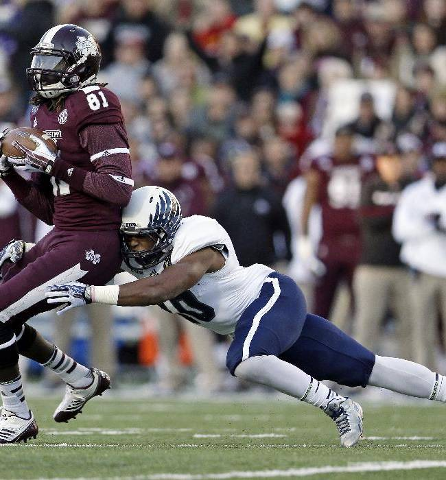 Mississippi State wide receiver De'Runnya Wilson (81) catches a pass for a 7-yard gain as he is hit by Rice safety Gabe Baker in the second quarter of the Liberty Bowl NCAA college football game on Tuesday, Dec. 31, 2013, in Memphis, Tenn