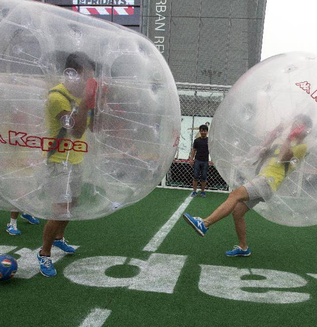 Chinese men play bubble soccer where players inside a plastic bubble kick a ball in Beijing, China, Friday, July 4, 2014. Retailers are taking advantage of the World Cup 2014 fever to promote their brand