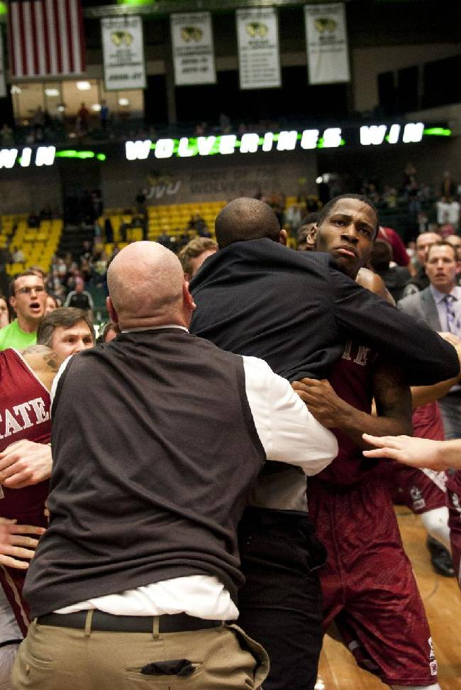 In this Thursday, Feb. 27, 2014 photo, security, at center back to camera, try to hold back players as a wild brawl involving players and fans who came onto the court broke out when New Mexico State guard K.C. Ross-Miller hurled the ball at Utah Valley's Holton Hunsaker seconds after the Wolverines' 66-61 overtime victory against the Aggies in Orem, Utah