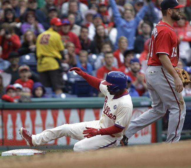Philadelphia Phillies' Jimmy Rollins,  left, slides safe into third on a triple as Washington Nationals' Kevin Frandsen waits for the ball in the first inning of a baseball game onSunday, May 4, 2014, in Philadelphia