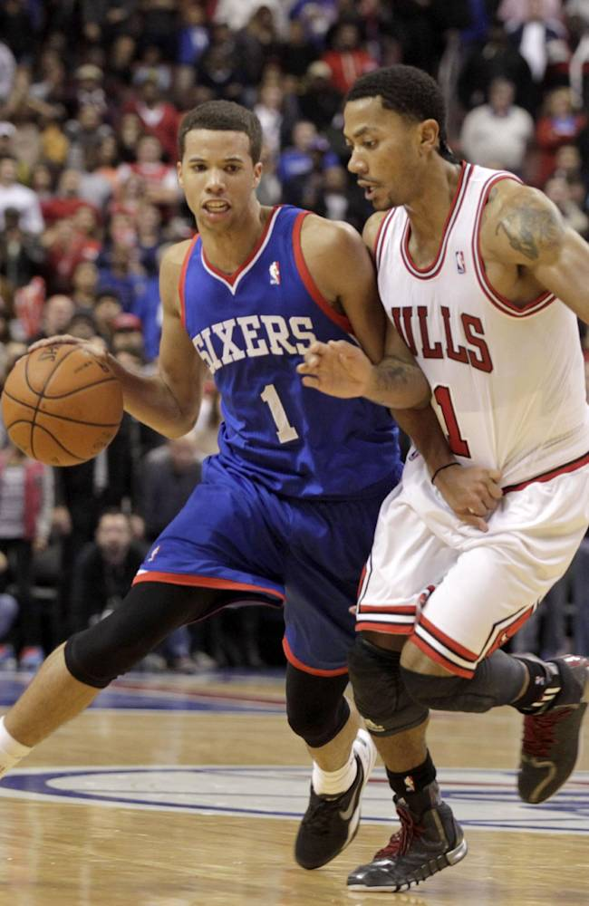 Chicago Bulls' Derrick Rose, right, defends as Philadelphia 76ers' Michael Carter-Williams (1) moves the ball up the court in the second half of an NBA basketball game Saturday Nov. 2, 2013, in Philadelphia.  The 76ers won 107-104