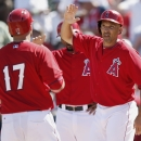 Los Angeles Angels' Chris Iannetta (17) comes in to score after hitting a three-run home run as teammates Raul Ibanez, right, and Howie Kendrick are ready with high-fives during the second inning of an exhibition spring training baseball game against the