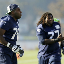 Seattle Seahawks offensive tackle Russell Okung, left, and offensive guard James Carpenter, right, work during warmups before NFL football practice Wednesday, Jan. 14, 2015 in Renton, Wash. The Seahawks will face the Green Bay Packers Sunday in the NFC Ch