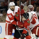 Chicago Blackhawks' Jonathan Toews (19) battles for position in front of the goal with Detroit Red Wings' Henrik Zetterberg (40) during the second period of Game 2 of the NHL hockey Stanley Cup playoffs Western Conference semifinals in Chicago, Saturday, May 18, 2013. (AP Photo/Nam Y. Huh)