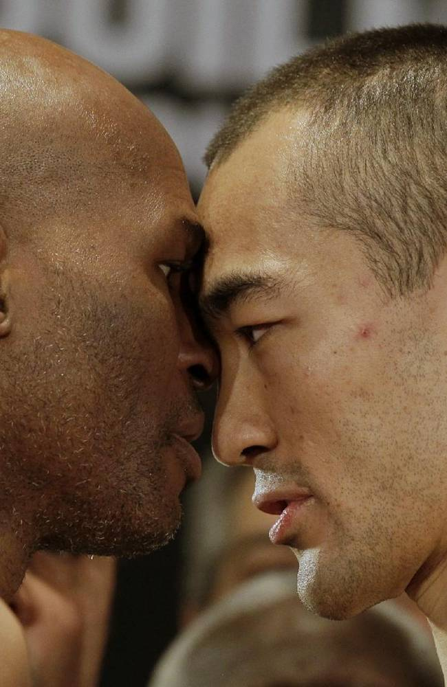 IBF light heavyweight boxing champion Bernard Hopkins, left, faces off with WBA and IBA light heavyweight boxing champion Beibut Shumenov, of Kazakhstan,after a weigh-in Friday, April 18, 2014, in Washington. Hopkins will fight Shumenov in a unification title match Saturday, April 19, 2014, in Washington