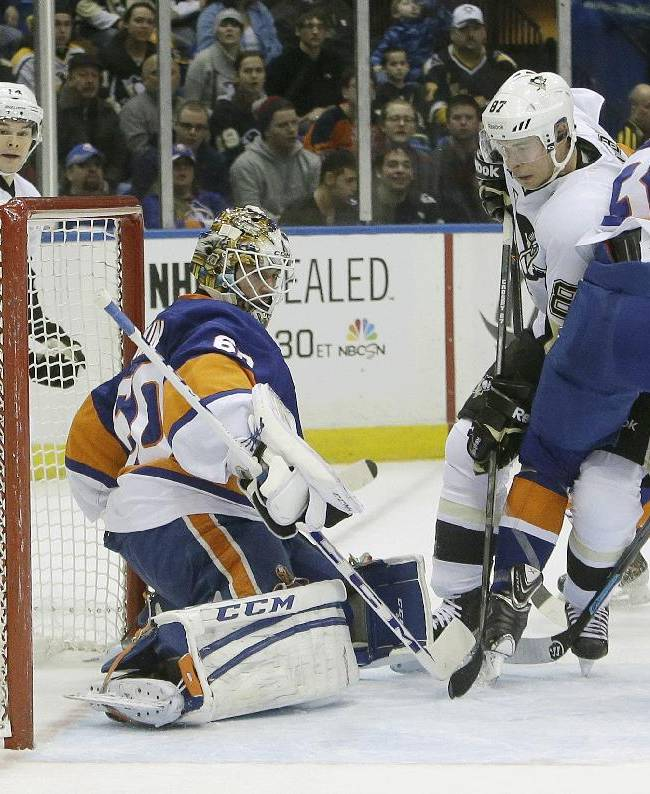 Pittsburgh Penguins' Sidney Crosby (87) shoots the puck past New York Islanders goalie Kevin Poulin (60) during the first period of an NHL hockey game Thursday, Jan. 23, 2014, in Uniondale, N.Y