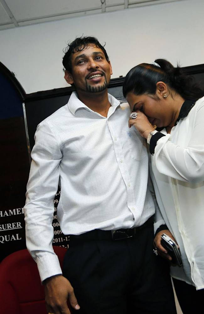 Ex-Sri Lankan captain Tillakaratne Dilshan, left, consoles his wife Manjula Thilini after a media briefing in Colombo, Sri Lanka, Thursday, Oct. 10, 2013. Dilshan announced his retirement from test cricket with immediate effect on Thursday, saying he wants to clear the way for younger players