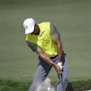 Tiger Woods hits from an 18th hole bunker during the first round of the Cadillac Championship golf tournament Friday, March 7, 2014, in Doral, Fla. A severe thunderstorm delayed first round play during on Thursday. (AP Photo/Wilfredo Lee)