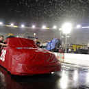 The crew of driver Bryan Dauzat pushes his truck to the hauler after inclement weather postponed the NASCAR UNOH 200 Truck Series auto race on Wednesday, Aug. 20, 2014, in Bristol, Tenn. until Thursday. (AP Photo/WADE PAYNE)
