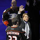Former Anaheim Ducks player Teemu Selanne, of Finland, waves with defenseman Francois Beauchemin (23) and center Ryan Getzlaf, above left, looking on, as Selanne walks on the ice to a team ceremony to retire and raise his No. 8 jersey banner before an NHL