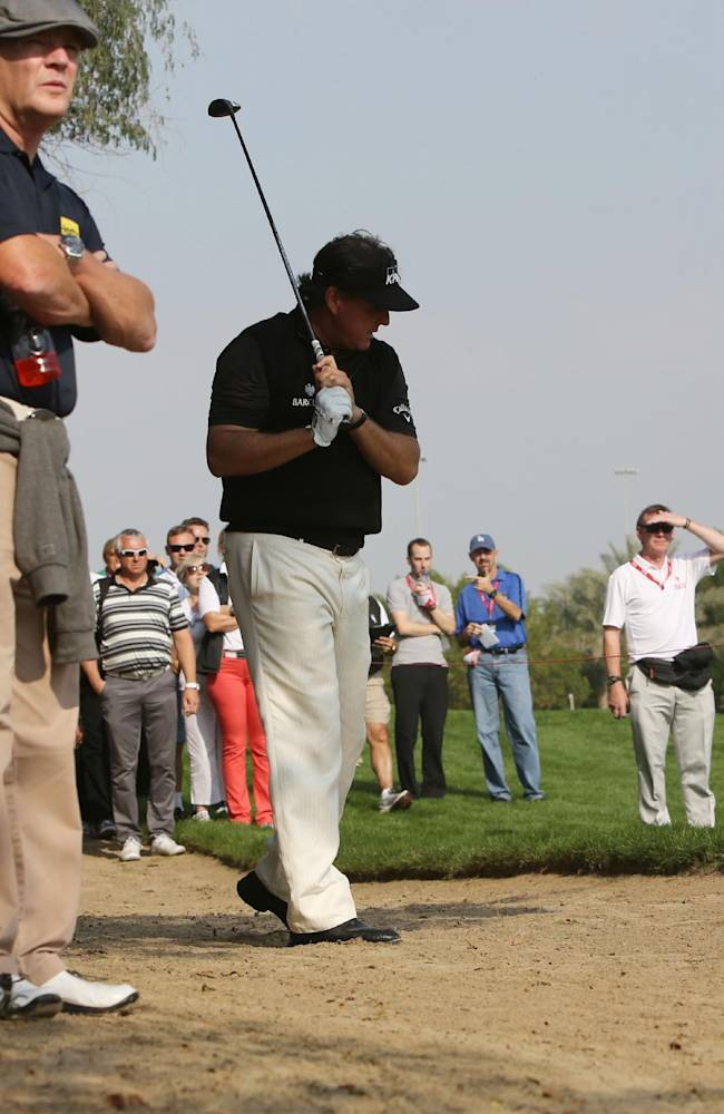 Phil Mickelson of the U.S. reacts after he plays a ball on the 2nd hole during the 1st round of the Abu Dhabi HSBC Golf Championship in Abu Dhabi, United Arab Emirates, Thursday, Jan. 16, 2014