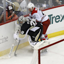Pittsburgh Penguins goalie Marc-Andre Fleury (29) tries to control the puck along the boards in front of Carolina Hurricanes' Manny Malhotra (22) during the third period of an NHL hockey game onTuesday, April 1, 2014, in Pittsburgh. The Hurricanes won 4-1