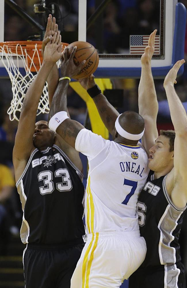 Golden State Warriors center Jermaine O'Neal goes to the basket against San Antonio Spurs forwards Boris Diaw, left, and Aron Baynes, right, during the first quarter of their NBA basketball game Saturday, March 22, 2014, in Oakland, Calif