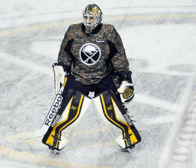 Buffalo Sabres goaltender Jhonas Enroth, of Sweden, looks up into the crowd as he skates at center ice in a camouflage uniform during warm ups before an NHL hockey game against the Los Angeles Kings in Buffalo, N.Y., Tuesday, Nov. 12, 2013