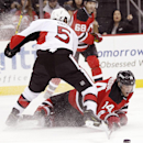 New Jersey Devils center Adam Henrique (14) hits the ice while attacking against Ottawa Senators defenseman Cody Ceci (5) during the second period of an NHL hockey game, Wednesday, Dec. 17, 2014, in Newark, N.J The Associated Press