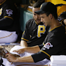 Pittsburgh Pirates starting pitcher Charlie Morton cleans the mud out of his cleats as he talks with catcher Russell Martin in the dugout after pitching the fourth inning of a baseball game against the Milwaukee Brewers in Pittsburgh on Friday, April 18,