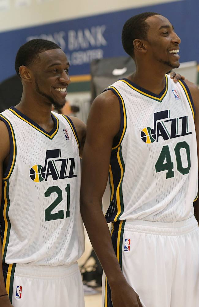 Utah Jazz players Ian Clark, left, and Jeremy Evans watch other players have their picture taken at the NBA basketball teams media day in Salt Lake City, Friday, Sept. 30, 2013