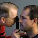 Ottawa Senators' Chris Phillips has his eyes examined during the opening day of the NHL hockey training camp in Ottawa on Thursday, Sept. 18, 2014 The Associated Press