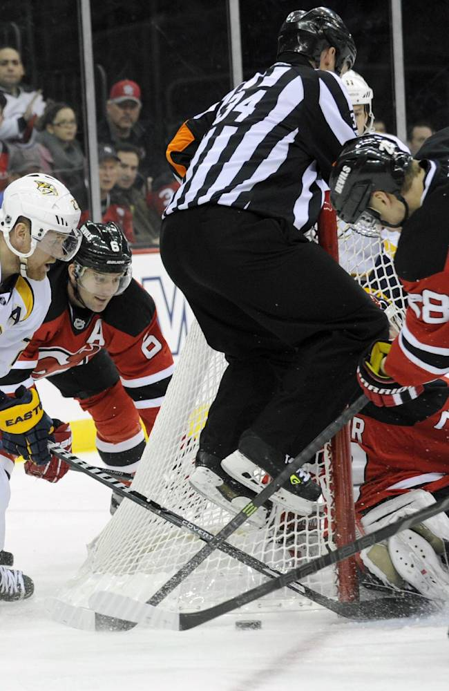 Referee Brad Meier. center, jumps onto the net as Nashville Predators' Patric Hornqvist, left, of Sweden, and New Jersey Devils Anton Volchenkov, right, of Russia, battle for the puck during the first period of an NHL hockey game on Sunday, Nov. 10, 2013, in Newark, N.J