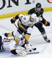 Nashville Predators goalie Carter Hutton (30) dives on the puck in front of Predators defenseman Mattias Ekholm (42) and Minnesota Wild left wing Matt Cooke, right, during the first period of an NHL hockey game in St. Paul, Minn., Sunday, April 13, 2014. (AP Photo/Ann Heisenfelt)