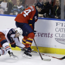 Columbus Blue Jackets left wing Matt Calvert (11) and Florida Panthers defenseman Erik Gudbranson (44) go for the puck during the third period of an NHL hockey game, Thursday, Dec. 4, 2014, in Sunrise, Fla. The Columbus Blue Jackets defeated the Florida