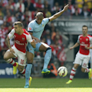 Arsenal's Jack Wilshere, left competes for the ball with Manchester City's Fernando Fracisco Reges during the English FA Community Shield soccer match at Wembley Stadium, London Sunday, Aug. 10, 2014
